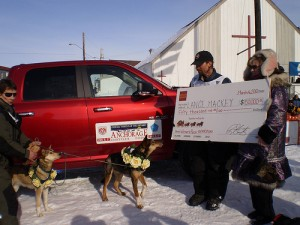 Lance Mackey poses with winner's check and the new truck he won. Photo attributed to jkbrooks85 on flickr.